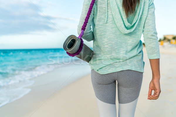 Fitness beach woman carrying yoga mat with strap Stock photo © Maridav