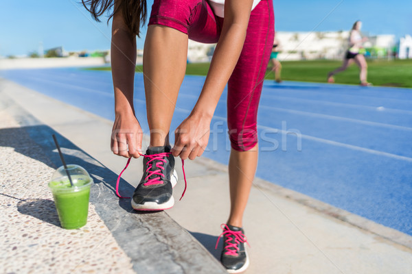 Running woman tying shoes drinking green smoothie Stock photo © Maridav