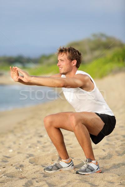 Fitness man training air squat exercise on beach Stock photo © Maridav