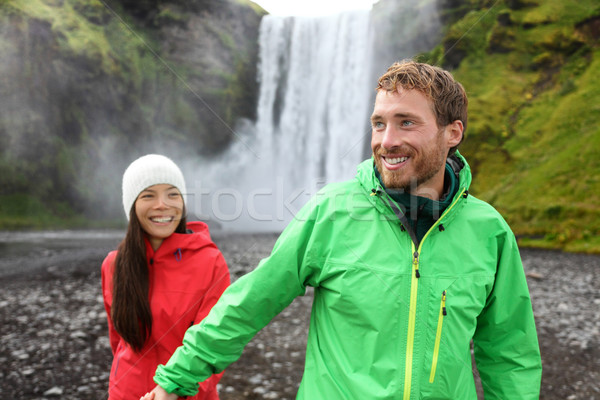Happy couple holding hands by waterfall outdoors Stock photo © Maridav