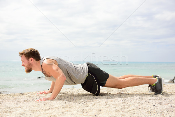 Push-ups - man fitness exercising on beach Stock photo © Maridav