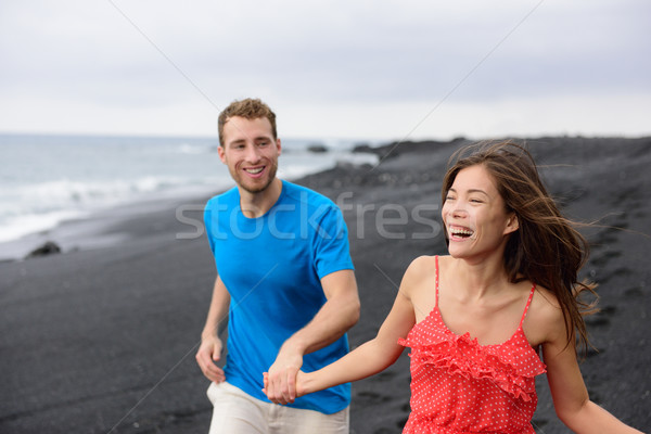 Happy couple laughing together walking on beach Stock photo © Maridav