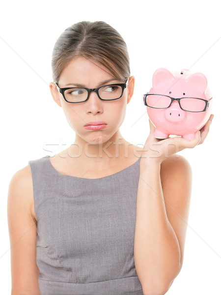 Upset woman wearing glasses holding piggy bank Stock photo © Maridav