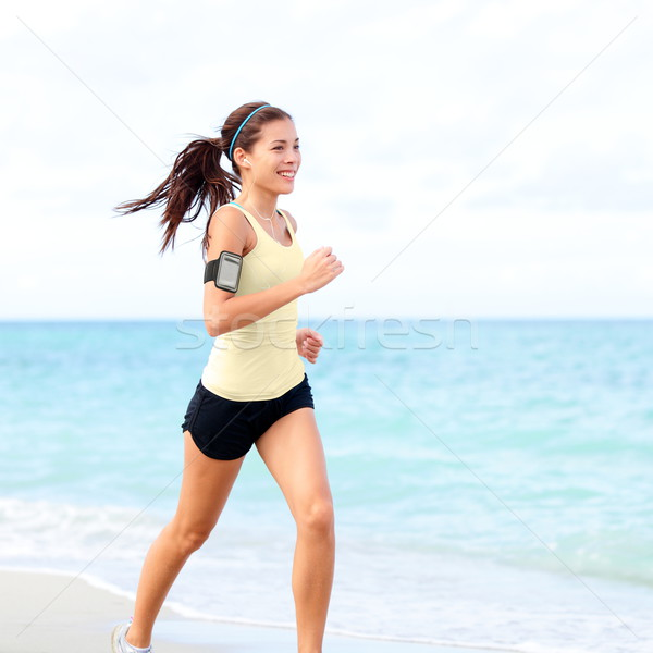 Running woman jogging on beach listening to music Stock photo © Maridav