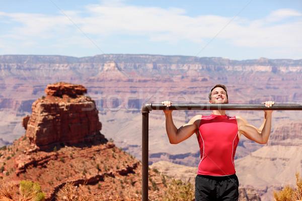 Fitness athlete training pull ups in Grand Canyon Stock photo © Maridav