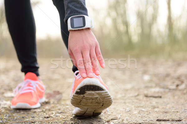 Runner stretching leg before run with smartwatch Stock photo © Maridav