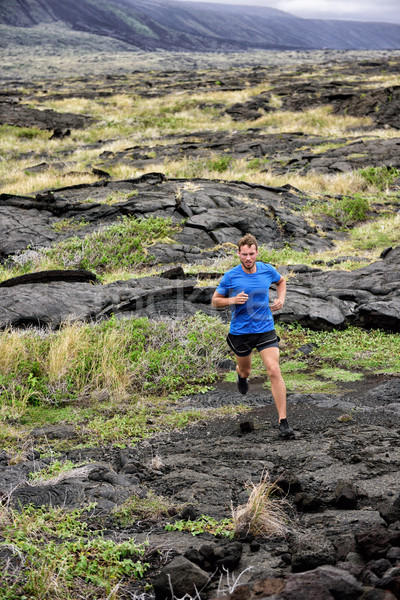 Stock photo: Active man trail running on volcanic rocks