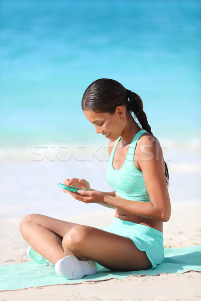 Fit girl using fitness app on phone texting during travel holidays on beach Stock photo © Maridav