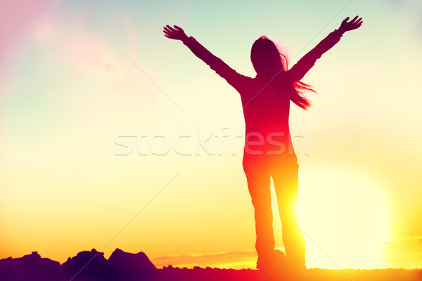 Happy success winning woman arms up at sunset Stock photo © Maridav