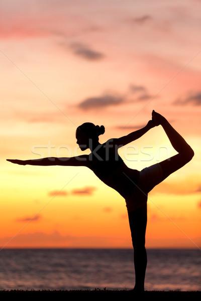 Yoga woman in serene sunset at beach doing pose Stock photo © Maridav