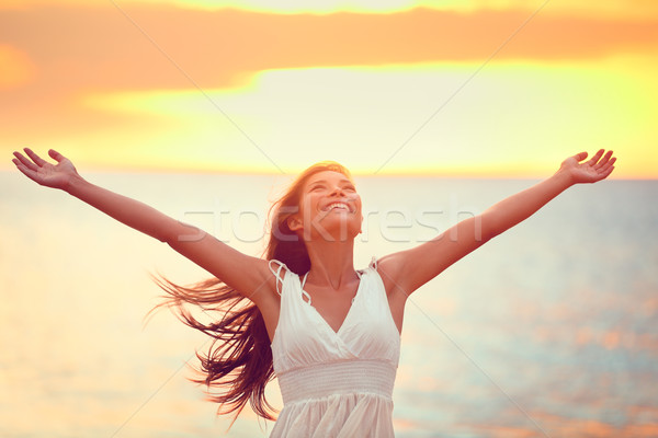 Free happy woman praising freedom at beach sunset Stock photo © Maridav