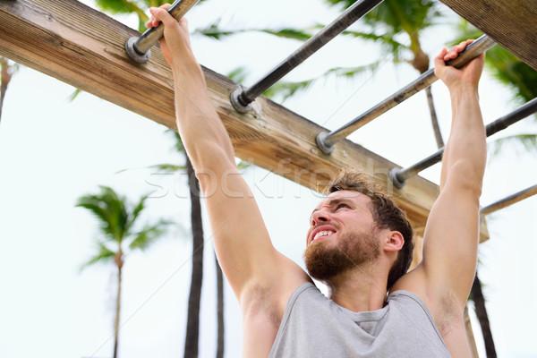 Exercise fitness athlete exercising on monkey bars Stock photo © Maridav