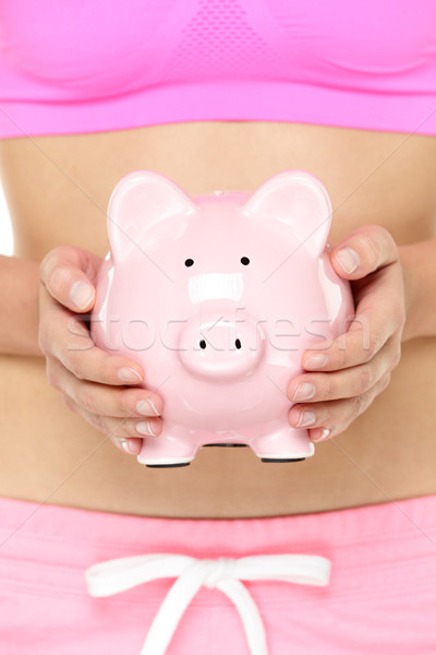 Piggy bank in front of stomach Stock photo © Maridav