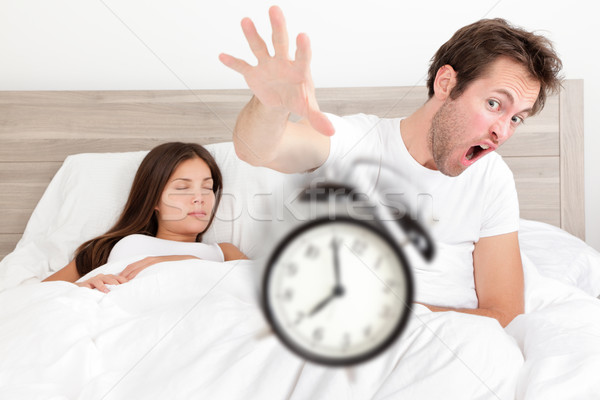 Wake up - couple waking up early throwing alarm Stock photo © Maridav