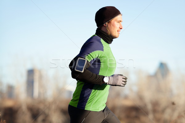 Running man jogging in autumn to music on phone Stock photo © Maridav