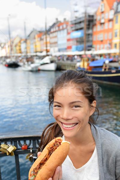 Woman eating traditional danish fast food hot dog Stock photo © Maridav