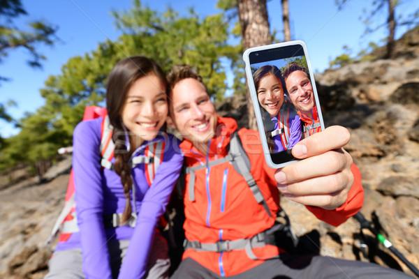 Selfie couple using smart phone hiking in nature Stock photo © Maridav
