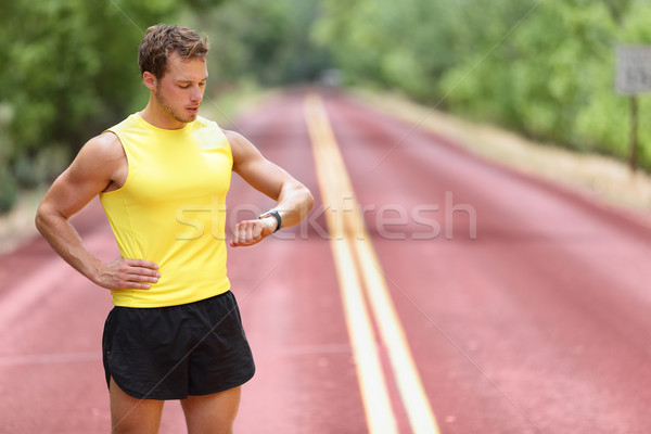 Stock photo: Runner looking at smartwatch heart rate monitor