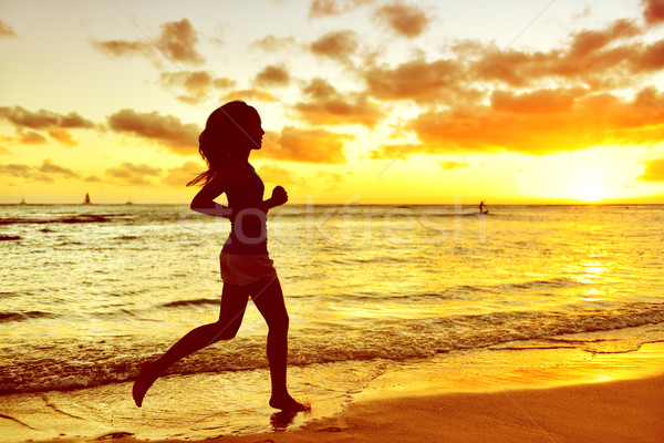 Silhouette Woman Jogging At Beach During Sunrise Stock photo © Maridav