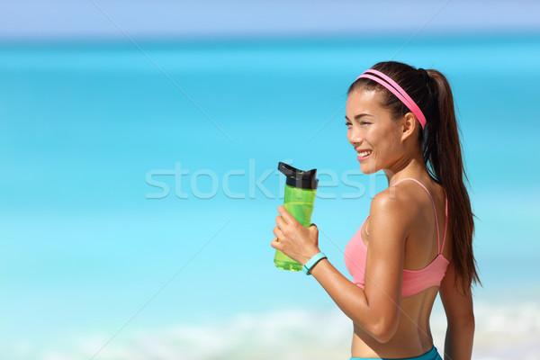 Healthy fitness runner girl drinking water bottle Stock photo © Maridav
