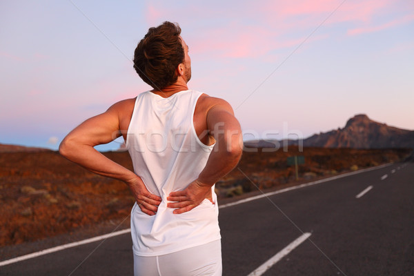 Back pain - Athletic running man with injury Stock photo © Maridav