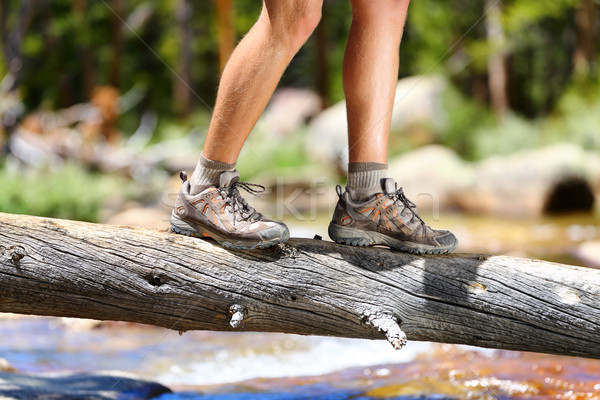 Hiking shoes - man hiker balancing crossing river Stock photo © Maridav