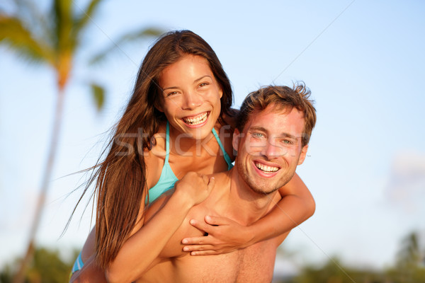 Vacation couple fun on beach, man giving piggyback Stock photo © Maridav