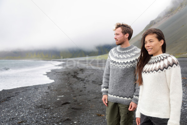 Iceland couple wearing Icelandic sweaters on beach Stock photo © Maridav