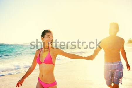 Stock photo: Pretty couple holding hands on beach woman smiling