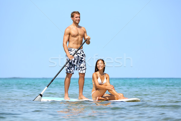 Beach fun couple on stand up paddleboard Stock photo © Maridav