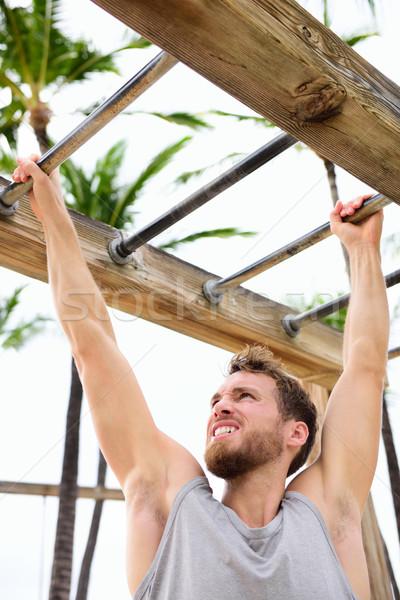Workout man working out arms on brachiation ladder Stock photo © Maridav