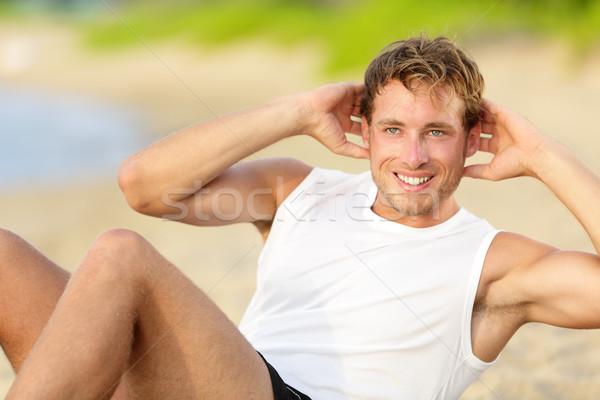 Fitness man doing crunches sit-ups on beach Stock photo © Maridav