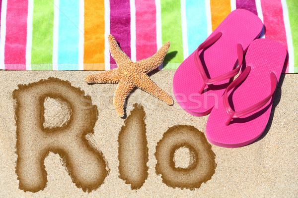 Rio written on beach sand with a colorful towel Stock photo © Maridav
