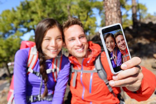 Selfie couple using smart phone camera hiking Stock photo © Maridav