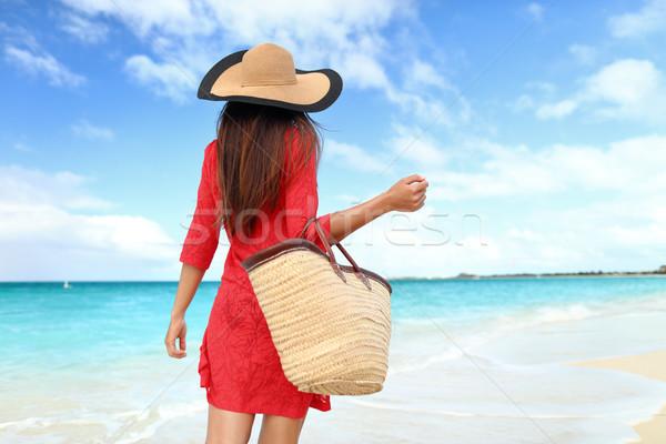 Beach tourist wearing sun hat, dress and bag Stock photo © Maridav
