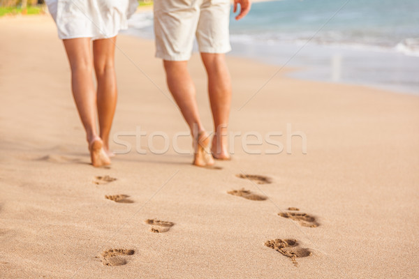 Beach couple walking barefoot on sand - footprints Stock photo © Maridav