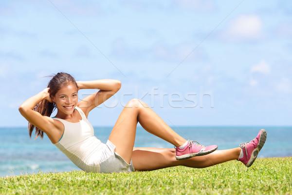 Exercising fitness woman doing sit ups outside Stock photo © Maridav