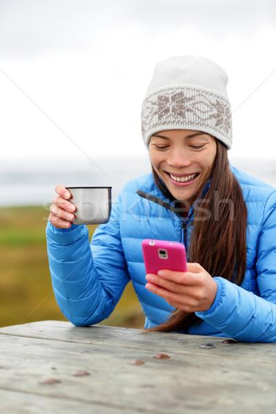 Woman outdoors using smart phone drinking coffee Stock photo © Maridav