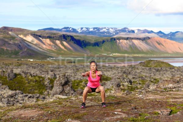 Fitness girl exercising outdoors doing jump squat Stock photo © Maridav
