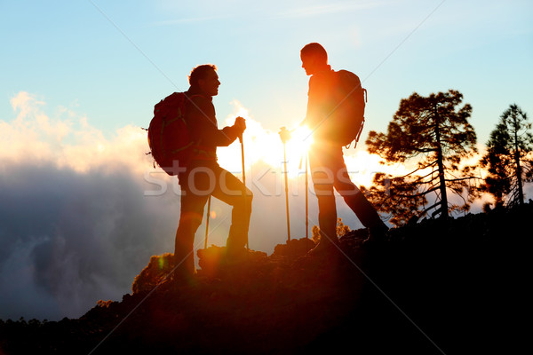 Hiking couple looking enjoying sunset view on hike Stock photo © Maridav