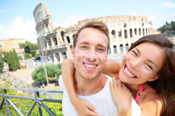 Happy travel couple in piggyback by Coliseum, Rome Stock photo © Maridav