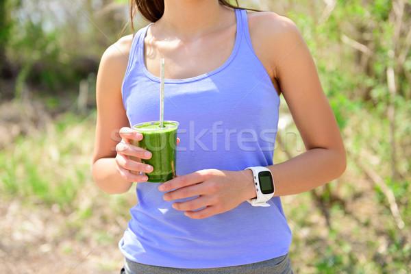 Green smoothie - woman runner wearing smartwatch Stock photo © Maridav