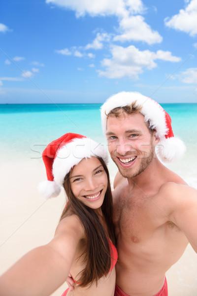 Christmas couple taking selfie on beach holidays Stock photo © Maridav