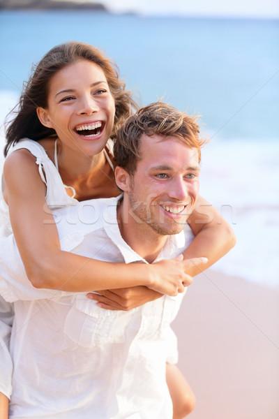 Happy couple piggybacking on beach. Stock photo © Maridav