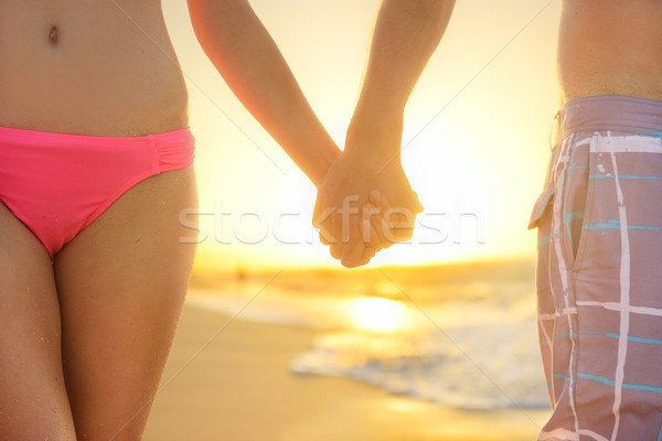 Stock photo: Love - romantic couple holding hands, beach sunset