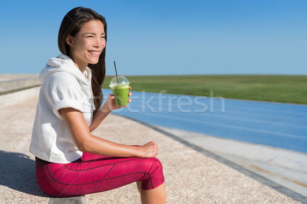 Healthy Asian athlete drinking green smoothie cup Stock photo © Maridav