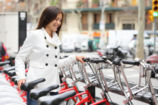 City bike - woman using public city bicycles Stock photo © Maridav