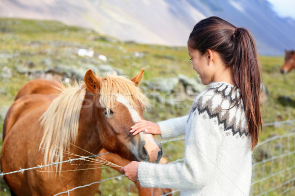 Icelandic horses - woman petting horse on Iceland Stock photo © Maridav