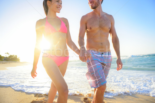 Stock photo: Attractive young couple walking on tropical beach