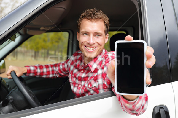 Smartphone man driving car showing app on screen Stock photo © Maridav